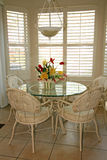 Bright dining room with shutters. A brightly lit dining area with five chairs and a glass table, tile floor, and white shutters.  Silk flowers are on the table Royalty Free Stock Photography