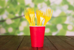 Bright disposable paper cup and plastic forks on abstract green. Royalty Free Stock Photography