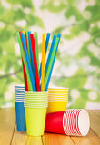 Bright disposable paper cups and straws on abstract green. Stock Images