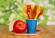 Bright disposable tableware and apple on  abstract green background. Royalty Free Stock Images