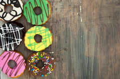 Bright donuts on wooden background royalty free stock image