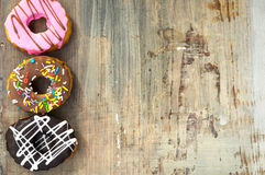 Bright donuts on wooden background royalty free stock photos