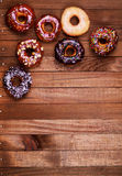 Bright donuts on wooden background. Stock Image
