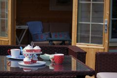 Tea and cakes served outdoors in the garden, in front of a summer house. Bright dotty crockery, placed on a glass outdoor table, serving tea and cupcakes on a stock photography