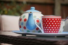 Tea served outdoors in the garden, in pretty dotty crockery. Bright dotty crockery, placed on a glass outdoor table, serving tea in the garden on a summers day stock image