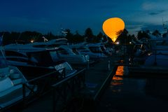 Bright earostat against dark evening sky near port with cutters. Summer entertainment concept. Adventure. Aircraft. Air balloon stock image