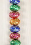 Bright easter eggs. Bright small easter eggs in a row on a wooden background Royalty Free Stock Images