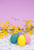 Bright Easter eggs on a floral patterned cloth Stock Images