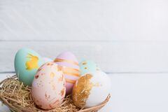 Free Bright Easter Eggs With In Basket, On White Wood Royalty Free Stock Images - 176150129