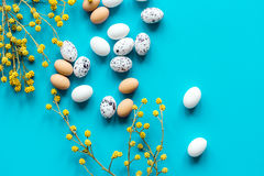 Bright easter set with eggs on blue background top view mock-up. Bright easter set with eggs and flower for cards on blue background top view mock-up Royalty Free Stock Images