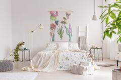 A bright eco friendly bedroom interior with a bed dresses in green plants pattern white linen. Fabric painted in flowers and birds. On the background wall. Real royalty free stock image