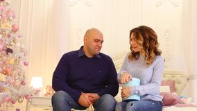 Bright emotions and cute moments of husband and wife, giving gifts on eve of holidays, sitting on bed in bedroom with. Handsome man happily hands gift blue box stock video footage
