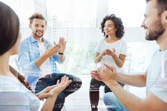 Optimistic coworkers clapping hands and smiling Stock Photo