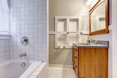 Bright empty bathroom interior with brown vanity cabinet. And mirror Royalty Free Stock Photo