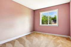 Bright empty room with one window, carpet floor and pink walls Royalty Free Stock Images