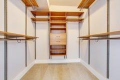 Bright empty walk-in closet with wood shelves, beige carpet floor. Stock Image