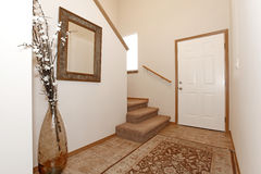 Bright entrance hall. Light wall entrance hall with a rug. Decorated with a mirror and vase with dry branches Stock Images