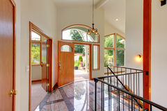 Bright entry way with tile floor and staircase with metal railings. Royalty Free Stock Photography