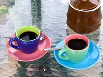 Bright espresso cups. Two very brightly colored espresso cups and a sugar pot ready to serve on a patio table Stock Photo