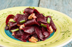 On a bright ethnic plate is a vegetarian lean beet salad, green Royalty Free Stock Photography