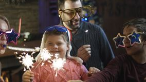 Bright excited family with sparkles having Christmas. Loving parents with kids wearing festive glasses and holding burning sparkles having fun on New Year stock images
