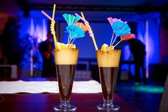 Bright exotic cocktails. Decorated with lemon, straws and umbrellas on the table in the restaurant Stock Image