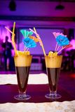 Bright exotic cocktails decorated with lemon, straws and umbrellas on the table. In the restaurant royalty free stock photography