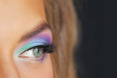 Bright eye makeup. Girl looks into the distance on a black background Stock Image