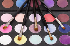 Bright eye shadow and cosmetic brushes. Stock Photo