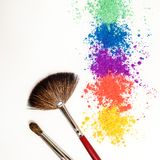 Bright eye shadows in different colors of the rainbow and brushes for cosmetics on a white background. royalty free stock images