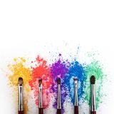 Bright eye shadows in different colors of the rainbow, scattered on a white background. stock photo