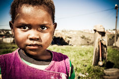 Bright eyed. Little african girl with big dark eyes playing outdoors in the township royalty free stock image
