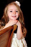 Bright Eyed Little Girl. A smile on a little blond bright eyed cute 5 year old girl with a bow in her long hair. Shallow depth of field dark background royalty free stock image