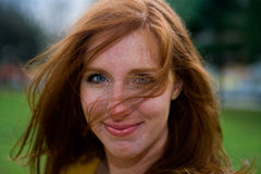 Bright Eyed Redhead. Portrait of blue eyed 24 year old caucasian redhead woman on a windy afternoon in New England, USA royalty free stock image