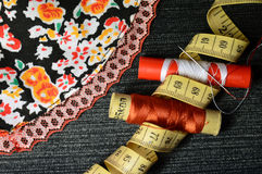 Bright fabrics, black jeans and sewing supplies stock image
