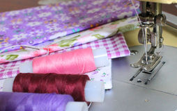 Bright fabrics, colorful spools of thread. And sewing machine royalty free stock images