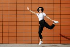 Bright fashion hipster young woman with stylish sunglasses and black hat jump near wall. Freedom concept. Stock Photography