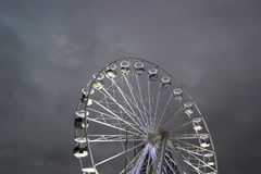 Bright ferris wheel against dark sky. Lit-up ferris wheel pleasure ride set against early evening grey cloudy sky Stock Image