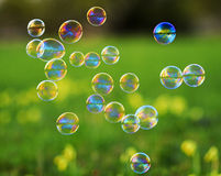 Bright festive background with flying shiny soap bubbles on gree Royalty Free Stock Photos