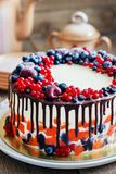 Bright festive cake with berries and chocolate on a dark wood background, rustic style Royalty Free Stock Photography