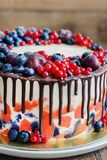 Bright festive cake with berries and chocolate on a dark wood background, rustic style Stock Photo