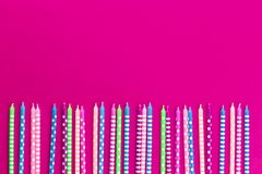 Row of colorful candles on neon pink background stock images