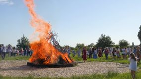 Bright festive fire on forest glade, folk festivities on open air on green glade, crowd of people near big great stock video
