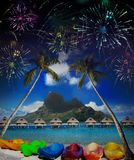 Bright festive fireworks over palm trees and the sea.  Stock Photo
