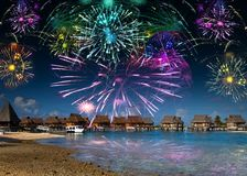 Bright festive fireworks over the sea and the beach Stock Photography