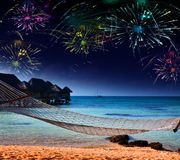 Bright festive fireworks over the sea and the beach Stock Photos