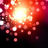 Bright festive red flash, glare and sparks on a black background. Stock Photos