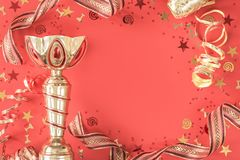 Bright festive trophy cup goblet and ribbons coral flat lay stock images