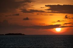 A bright fiery sunset on the ocean: a round ball of sun sets to the water amidst gray clouds, to the left is the black contour of. Bright fiery sunset on the Stock Photography