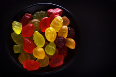 Bright figures of colorful marmalade in a black plate on a black background Stock Images